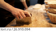 Купить «baker portioning dough with bench cutter at bakery», фото № 26910094, снято 15 мая 2017 г. (c) Syda Productions / Фотобанк Лори