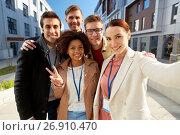 Купить «team with conference badges taking selfie in city», фото № 26910470, снято 13 мая 2017 г. (c) Syda Productions / Фотобанк Лори
