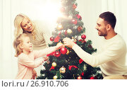 Купить «happy family decorating christmas tree at home», фото № 26910706, снято 8 октября 2015 г. (c) Syda Productions / Фотобанк Лори