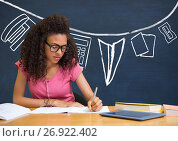 Купить «Student girl at table writing against blue blackboard with school and education graphic», фото № 26922402, снято 19 февраля 2020 г. (c) Wavebreak Media / Фотобанк Лори
