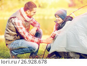 Купить «happy father and son setting up tent outdoors», фото № 26928678, снято 27 сентября 2015 г. (c) Syda Productions / Фотобанк Лори