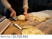 Купить «baker portioning dough with bench cutter at bakery», фото № 26928842, снято 15 мая 2017 г. (c) Syda Productions / Фотобанк Лори