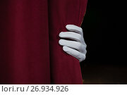 Купить «Hand in a white glove pulling curtain away», фото № 26934926, снято 20 апреля 2017 г. (c) Wavebreak Media / Фотобанк Лори