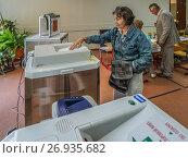 Купить «Москва. Жительница микрорайона Митино опускает бюллетень в урну на избирательном участке», эксклюзивное фото № 26935682, снято 10 сентября 2017 г. (c) Виктор Тараканов / Фотобанк Лори