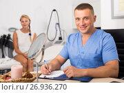 Купить «Doctor is writing the conclusion about result of examination of female client», фото № 26936270, снято 7 августа 2017 г. (c) Яков Филимонов / Фотобанк Лори