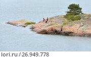 Семья с собакой на базальтовых скалах небольшого острова в Балтийском море. Аландские острова, Финляндия (2017 год). Редакционное фото, фотограф Валерия Попова / Фотобанк Лори