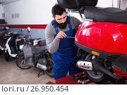Купить «Worker fixing failed scooter in motorcycle workplace», фото № 26950454, снято 25 сентября 2018 г. (c) Яков Филимонов / Фотобанк Лори