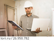 Купить «Professional constructor is standing with laptop and folder with documents», фото № 26950782, снято 18 мая 2017 г. (c) Яков Филимонов / Фотобанк Лори