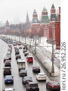 Плотный поток машин едет по заснеженной Кремлевской набережной (2013 год). Редакционное фото, фотограф Александр Гаценко / Фотобанк Лори