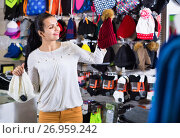 Купить «Female customer examining knit caps in sports store», фото № 26959242, снято 22 ноября 2016 г. (c) Яков Филимонов / Фотобанк Лори