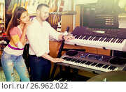 Купить «Saleswoman helping man to select synthesisers», фото № 26962022, снято 19 августа 2018 г. (c) Яков Филимонов / Фотобанк Лори