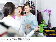 Купить «consultant offering customers autumn clothes in shop», фото № 26962082, снято 19 февраля 2019 г. (c) Яков Филимонов / Фотобанк Лори
