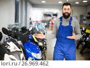 Купить «attractive man worker displaying various motorcycles in workshop», фото № 26969462, снято 21 сентября 2019 г. (c) Яков Филимонов / Фотобанк Лори