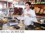 Купить «Female seller showing box of chocolate candies», фото № 26969526, снято 24 января 2017 г. (c) Яков Филимонов / Фотобанк Лори