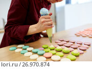 Купить «chef with injector squeezing filling to macarons», фото № 26970874, снято 8 мая 2017 г. (c) Syda Productions / Фотобанк Лори