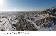 Купить «Aerial view of trucks and suvs moving along the highway in the desert in winter. Western Kazakhstan, Mangyshlak Peninsula.», видеоролик № 26972850, снято 9 мая 2017 г. (c) Вячеслав Позднышев / Фотобанк Лори