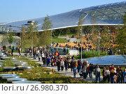 Купить «Moscow, Russia - September 23. 2017. People are walking in park Zaryadye against the background of glass bark.», фото № 26980370, снято 23 сентября 2017 г. (c) Володина Ольга / Фотобанк Лори