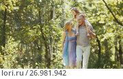 Купить «Father - bold man, mother - blonde beautiful woman and little girl - walking in the park at sunny day», фото № 26981942, снято 27 апреля 2018 г. (c) Константин Шишкин / Фотобанк Лори