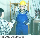 Купить «Constructor with spatula is clarifying details from client», фото № 26994086, снято 3 июня 2017 г. (c) Яков Филимонов / Фотобанк Лори