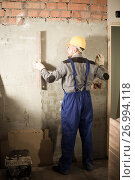 Купить «Professional constructor in helmet is measuring wall», фото № 26994118, снято 3 июня 2017 г. (c) Яков Филимонов / Фотобанк Лори