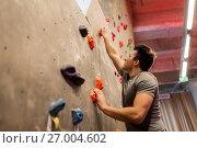 Купить «young man exercising at indoor climbing gym», фото № 27004602, снято 2 марта 2017 г. (c) Syda Productions / Фотобанк Лори