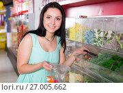 Купить «Happy girl in the store picks up candy in the bag», фото № 27005662, снято 25 апреля 2017 г. (c) Яков Филимонов / Фотобанк Лори