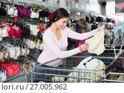 Купить «Smiling female customer choosing underwear», фото № 27005962, снято 18 июня 2019 г. (c) Яков Филимонов / Фотобанк Лори