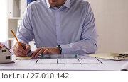 Купить «male architect with ruler measuring blueprint», видеоролик № 27010142, снято 11 сентября 2017 г. (c) Syda Productions / Фотобанк Лори