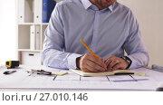 Купить «male architect with ruler measuring blueprint», видеоролик № 27010146, снято 11 сентября 2017 г. (c) Syda Productions / Фотобанк Лори