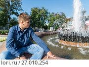 Купить «Teenager of 14 years is sitting near fountain», фото № 27010254, снято 31 августа 2017 г. (c) Володина Ольга / Фотобанк Лори