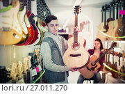Teenagers examining guitars in shop. Стоковое фото, фотограф Яков Филимонов / Фотобанк Лори