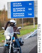 Купить «Девушка мотоциклист на фоне дорожного указателя расстояний на трассе Кола, Карелия», фото № 27012778, снято 24 сентября 2017 г. (c) Кекяляйнен Андрей / Фотобанк Лори
