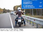 Купить «Мотоциклистка на мотоцикле на трассе Кола на фоне дорожного указателя расстояния до Санкт-Петербурга», фото № 27012786, снято 24 сентября 2017 г. (c) Кекяляйнен Андрей / Фотобанк Лори