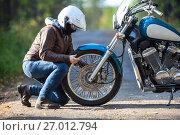 Девушка ремонтирует колесо на мотоцикле на грунтовой лесной дороге. Стоковое фото, фотограф Кекяляйнен Андрей / Фотобанк Лори