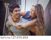 Купить «Millennial couple piggy back in alleyway», фото № 27015654, снято 18 октября 2018 г. (c) Wavebreak Media / Фотобанк Лори