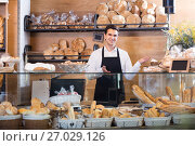 Купить «Male bakery employee offering bread and pastry», фото № 27029126, снято 12 августа 2018 г. (c) Яков Филимонов / Фотобанк Лори