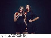 Купить «Attractive girls in the image of vampires hold glasses with blood. Halloween.», фото № 27029994, снято 22 сентября 2017 г. (c) Женя Канашкин / Фотобанк Лори