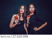 Купить «Attractive girls in the image of vampires hold glasses with blood. Halloween.», фото № 27029998, снято 22 сентября 2017 г. (c) Женя Канашкин / Фотобанк Лори
