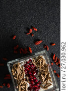 Yogurt, cereal bran sticks and pomegranate seeds in tray with dried fruits. Стоковое фото, агентство Wavebreak Media / Фотобанк Лори