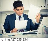 Young man is reading documents about the transaction. Стоковое фото, фотограф Яков Филимонов / Фотобанк Лори