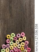 Купить «Froot loops arranged on wooden table», фото № 27036558, снято 13 июня 2017 г. (c) Wavebreak Media / Фотобанк Лори