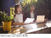 Купить «Smiling young creative professionals talking while sitting with laptop at coffee shop», фото № 27037478, снято 21 мая 2017 г. (c) Wavebreak Media / Фотобанк Лори