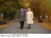 Купить «Пожилая семейная пара гуляют в осеннем парке», фото № 27037774, снято 1 октября 2017 г. (c) Иван Карпов / Фотобанк Лори
