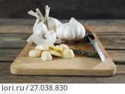 Купить «Garlics, rosemary and knife on chopping board», фото № 27038830, снято 5 июня 2017 г. (c) Wavebreak Media / Фотобанк Лори
