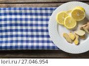 Купить «Lemon and ginger in plate on table», фото № 27046954, снято 12 июня 2017 г. (c) Wavebreak Media / Фотобанк Лори
