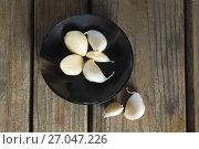 Купить «Garlics in plate on wooden table», фото № 27047226, снято 5 июня 2017 г. (c) Wavebreak Media / Фотобанк Лори