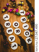 Купить «Cookies with trick or treat text by chocolates and decorations on table», фото № 27047490, снято 26 мая 2017 г. (c) Wavebreak Media / Фотобанк Лори