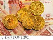 Золотые монеты криптовалюты Биткоин лежат на пятитысячных рублевых купюрах. Стоковое фото, фотограф Николай Винокуров / Фотобанк Лори