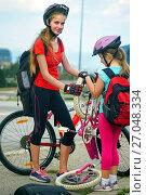 Купить «Children girls wearing helmet children repair bicycle.», фото № 27048334, снято 7 апреля 2016 г. (c) Gennadiy Poznyakov / Фотобанк Лори