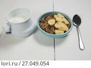 Купить «Wheat flakes and banana slice in bowl with milk jug», фото № 27049054, снято 13 июня 2017 г. (c) Wavebreak Media / Фотобанк Лори